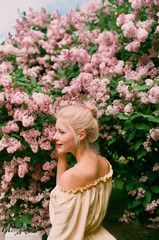 Young blonde woman among spring blossom