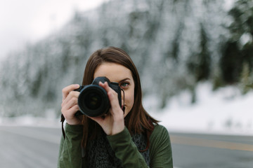 Woman Focusing Camera in Winter Landscape