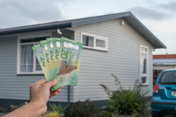 Cropped shot of man hand showing NZ dollar bills in front of house in New Zealand.