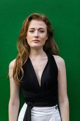 Striking freckled redhead woman against green wall