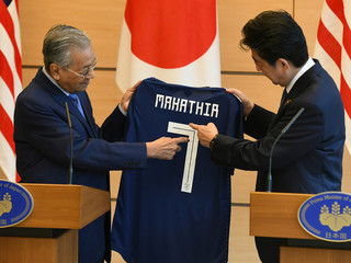 Malaysian Prime Minister Mahathir Mohamad receives a  Japanese national football jersey as a present from his Japanese counterpart Shinzo Abe during their joint press remarks in Tokyo