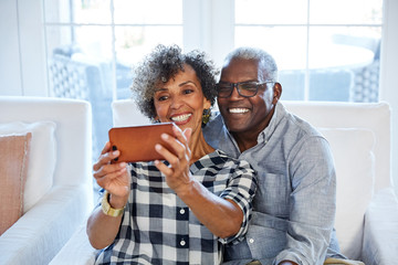 African American senior couple taking a selfie with a camera phone in their living room at home