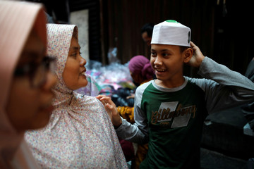 A boy tries on a new cap while shopping in Tanah Abang traditional market ahead of the upcoming Eid al-Fitr holiday marking the end of the Muslim holy month of Ramadan in Jakarta