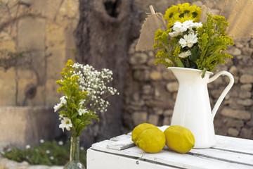 Yellow lemons with white jar lemon juice with plants decoration