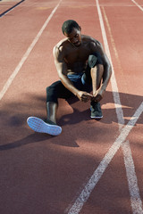 African american athlete tying his shoes  in the track and field