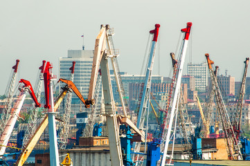 Port cranes, in the background the city is blurred due to the heat from the pipes of the ships