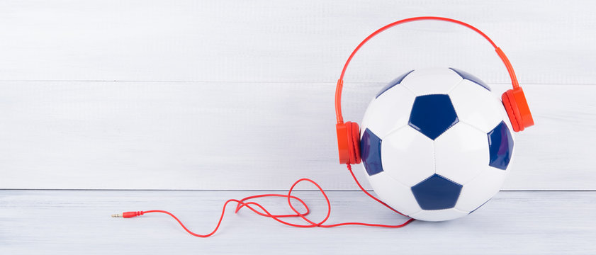 soccer ball with red headphones, with a place for writing, on a gray background
