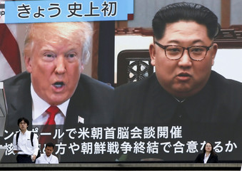 Passersby walk past in front of a huge TV screen reporting the summit between the U.S. and North Korea, in Tokyo