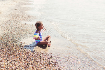 Young pretty child meditating contently on a sandy beach