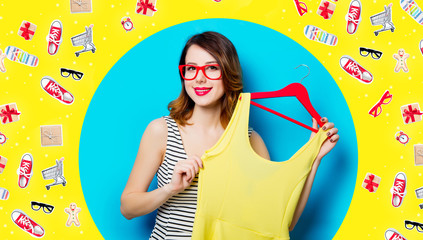 portrait of beautiful young woman with dress on hanger on the wonderful blue studio background and with clothes