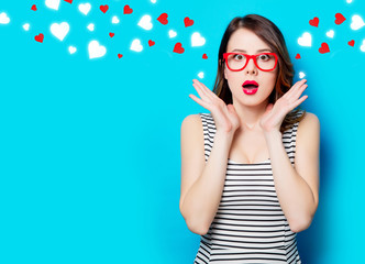 portrait of beautiful surprised young woman in glasses on the wonderful blue studio background and abstract hearts Wall mural