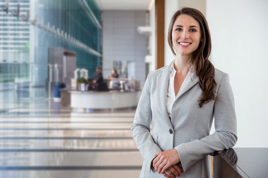 Cute commercial business corporate representative woman model brunette smiling in large building hall lobby