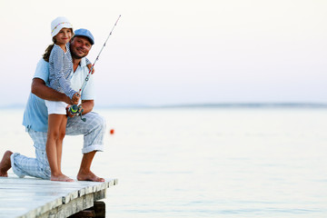 Father with his daughter fishing in a sea on a wood pier at sunset.