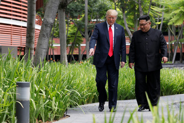 U.S. President Donald Trump and North Korean leader Kim Jong Un walk after lunch at the Capella Hotel on Sentosa island in Singapore