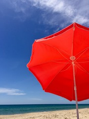 Red umbrella on a beach over blue sky