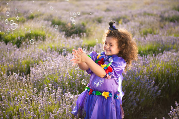 pretty little girl in fairy hat and dress playing soap bubbles in lavender field