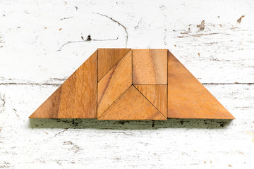 Tangram puzzle in trapezoid or trapezium shape on old white wood background