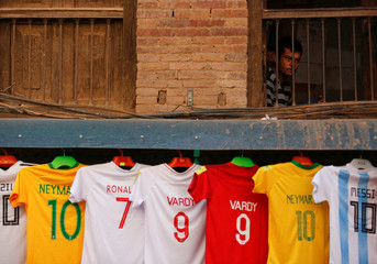 Jerseys of various players playing at the World Cup are kept on sale outside a shop ahead of the FIFA World Cup, in Bhaktapur