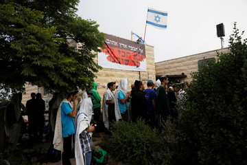 Protestors pray before Israeli security forces come to evacuate 15 Jewish settler families from the illegal outpost of Netiv Ha'avot in the Israeli occupied West Bank