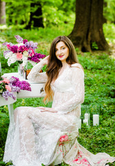 Amazing bride in a white dress sitting at the table with flowers