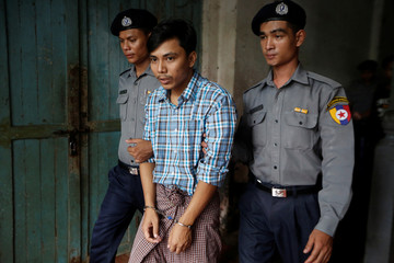 Detained Reuters journalist Kyaw Soe Oo is escorted by police out of the court hearing in Yangon