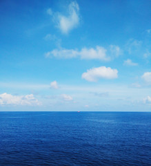 White fluffy clouds in the blue sky,breezy,Fresh on all day.Seeing a small boat.