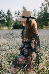 Side view portrait of young woman in black dress with floral print walking throw the field of white flowers and hiding her half of her face with straw hat