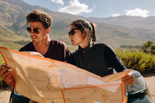 Young couple looking at map searching route
