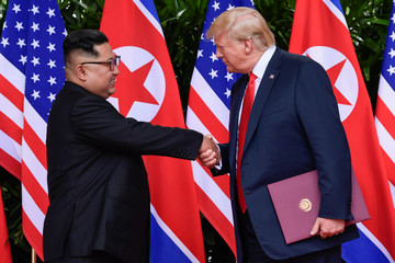 U.S. President Donald Trump and North Korea's leader Kim Jong Un shake hands during the signing of a document after their summit at the Capella Hotel on Sentosa island in Singapore