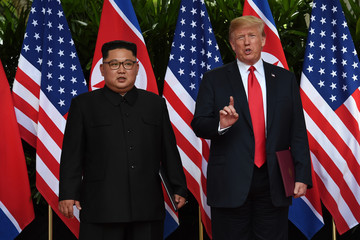 U.S. President Donald Trump and North Korea's leader Kim Jong Un react during their summit at the Capella Hotel on Sentosa island in Singapore