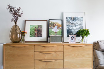 Sideboard with photographs and vase in living room