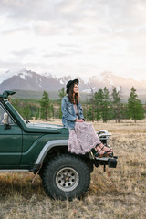 Young woman sitting on the old jeep parked in the wild area
