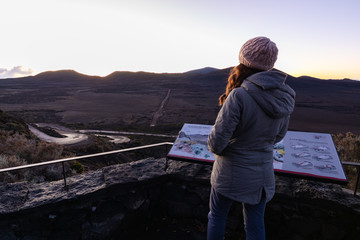 Girl watching the sunrise over the Plaine des Sables in Reunion Island