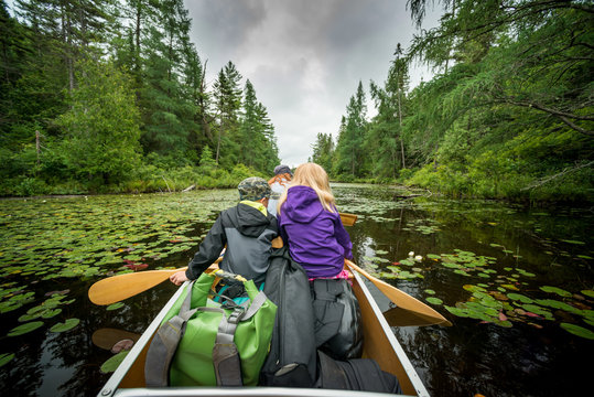 Woman and Children Paddling Canoe on Wilderness Canoe Trip Backcountry Camping
