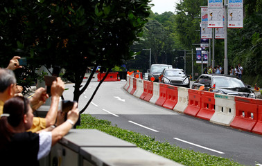 Members of the public watch the motorcade of North Korea's leader Kim Jong Un heading back to St. Regis Hotel in Singapore