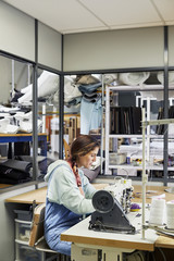 Female Worker Using Sewing Machine In Sofa Workshop