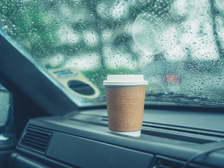 Paper cup of coffee on dashboard