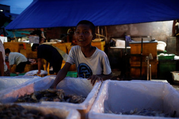 Children work at San Pya seafood wholesale market early in the morning in Yangon