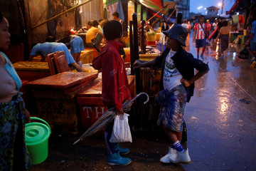 Children work at the San Pya seafood wholesale market early in the morning in Yangon