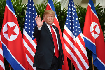 U.S. President Donald Trump waves during his meeting with North Korea's leader Kim Jong Un at their summit at the Capella Hotel on Sentosa island in Singapore