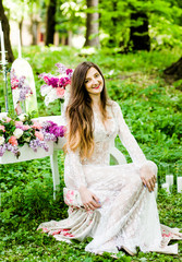 Cool bride in a white dress sitting at the table with flowers