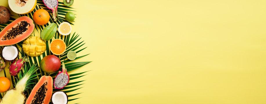 Exotic fruits and tropical palm leaves on pastel yellow background - papaya, mango, pineapple, banana, carambola, dragon fruit, kiwi, lemon, orange, melon, coconut, lime. Banner. Top view.
