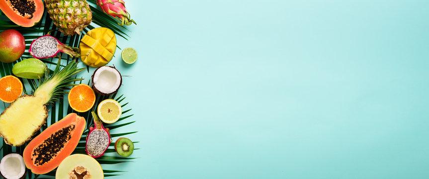 Exotic fruits and tropical palm leaves on pastel turquoise background - papaya, mango, pineapple, banana, carambola, dragon fruit, kiwi, lemon, orange, melon, coconut, lime. Banner. Top view.