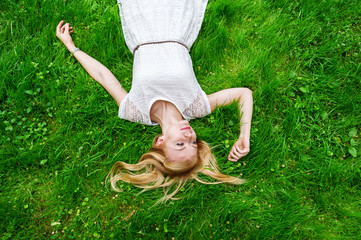 Beautiful young woman lying on the bright green grass.