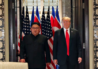 U.S. President Donald Trump and North Korea's leader Kim Jong Un arrive to sign documents after their summit in Singapore