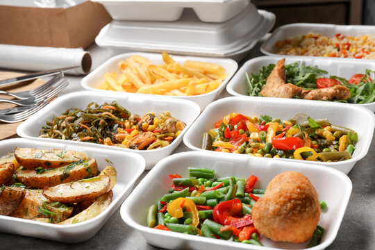 Foam plastic containers with delicious food on table