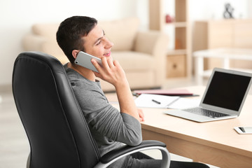 Young man talking on phone while working with laptop in home office