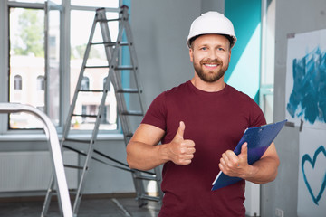 My occupation. Smiling bearded man wearing a helmet and showing a thumb up