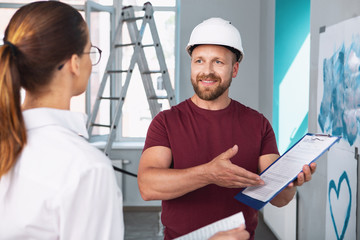 Contract terms. Inspired professional builder holding contract and talking with his client