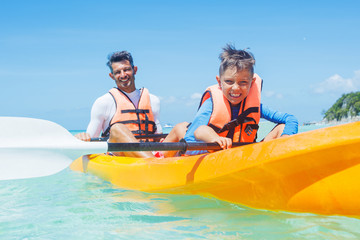 Happy boy and his father kayaking at tropical sea on yellow kayak